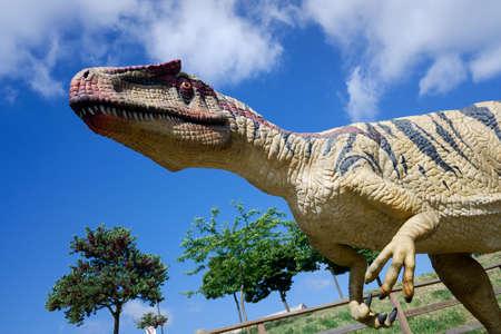 Recreation of an Allosaurus Fragilis, a dinosaur with large teeth, in an outdoor park.