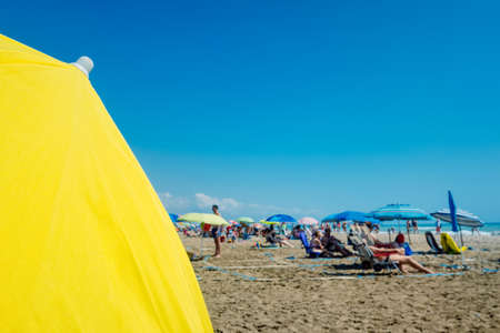 Beach holiday background, with a large yellow umbrella in the foreground and defocused bathers in the background. 免版税图像