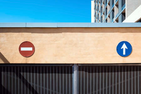 Direction and no-entry signs in a garage to guide traffic and indicate the correct path.