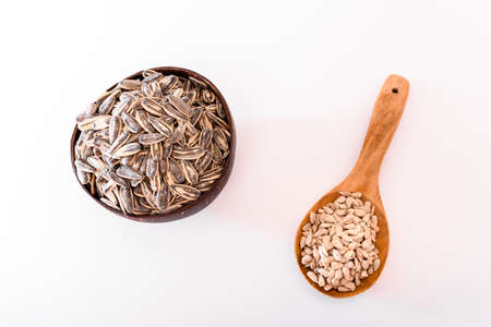 Peeled and raw unpeeled sunflower seeds in wooden spoon isolated on white background.