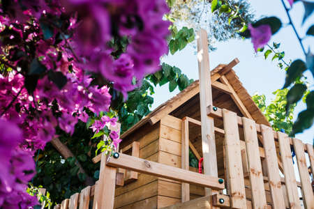 Raised wooden house for children's games in a private patio made with ecological woods. 免版税图像