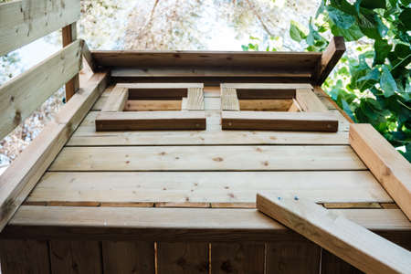 A wooden tree house with wooden boards for children's games.