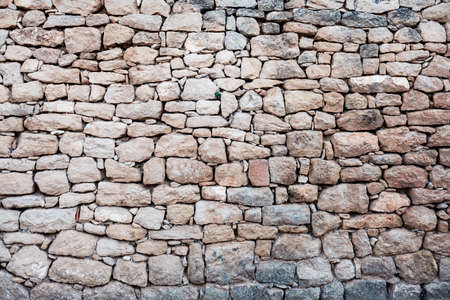 Stone wall with straight natural rocks, muted colors, rough background.