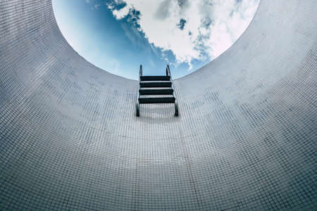 Sparse staircase of an empty pool, seen from below, minimalist tile background.