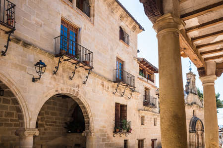 La Fresneda, Spain - July 11, 2021: Shaded atriums and patios between columns along the narrow streets of La Fresneda, Teruel. 新闻类图片