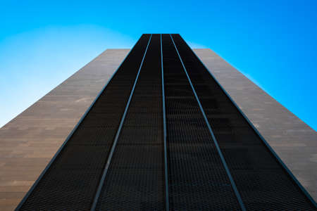 Symbolic tall building with a perspective of power, minimalist construction towards the blue sky, symmetrical design for contemporary backgrounds. 免版税图像