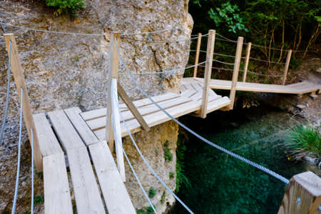 Wooden walkway next to some rocks on the bed of a river to facilitate the passage of tourists and walkers.