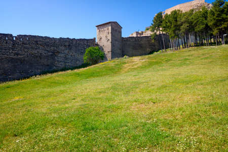 Ancient walls of a fortified city with a green grass meadow.