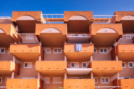 Facade of a block of holiday apartments on the beach, all with an outdoor balcony.