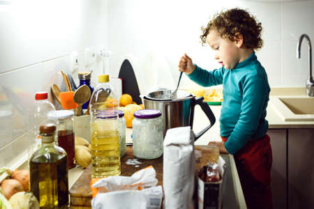 Adorable 2 year old girl cooking a cake at home overnight.