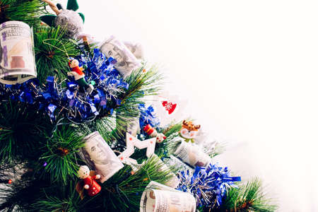 Detail of christmas tree with decorations and dollar bills wishing to earn money in the new year eve, with blank copy space. 免版税图像