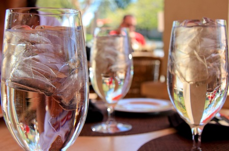 Three glasses of water with ice are standing on the dinner table.
