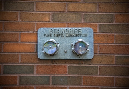 Silver-color standpipe is located on red bricks wall. Stock Photo