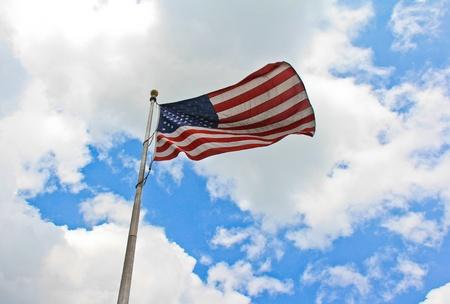 The US Flag on Deep Blue Skies Background.