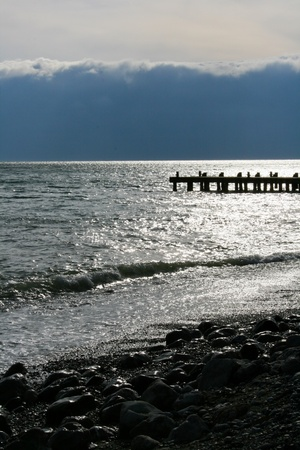 The view on stones on the beach of stormy sea. Stock Photo