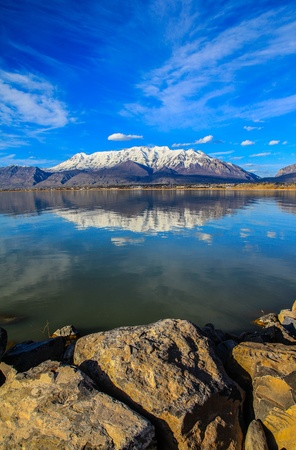 Gorgeous view on a lake and mountains  Great combination of rocks in front and mountains on background  Stock Photo