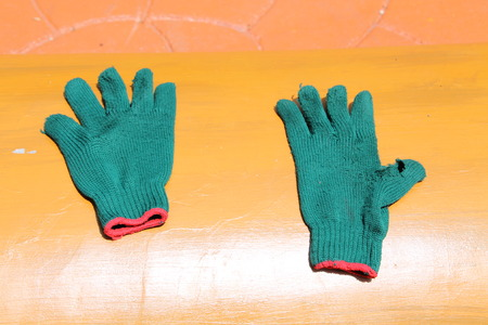 tatter: pair of green gloves on orange background