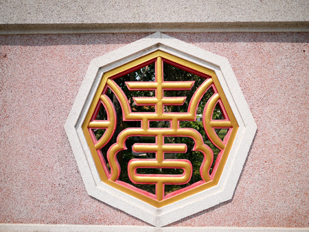 Chinese designed window on a wall of temple Stock Photo
