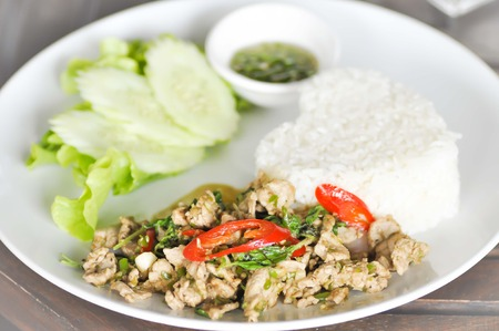Rice topped with stir fried minced pork and basil photo