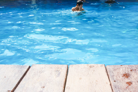 glum: man , wood terrace and swimming pool in blur background Stock Photo