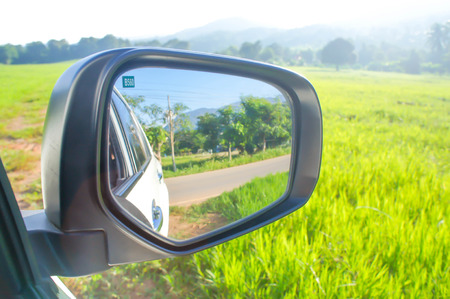 green field , mountain and the wing mirror of the car