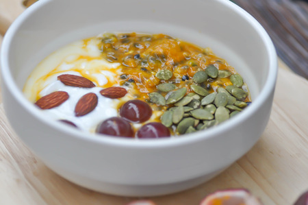 yogurt with passion fruit, almond ,sunflower seed and grape topping