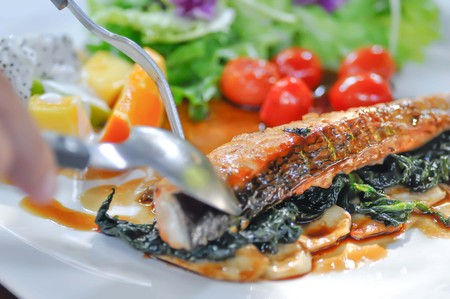 eating grilled salmon, salmon steak with vegetable