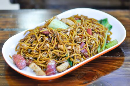 stir-fried noodles with pork, sausage and vegetable in Chinese style