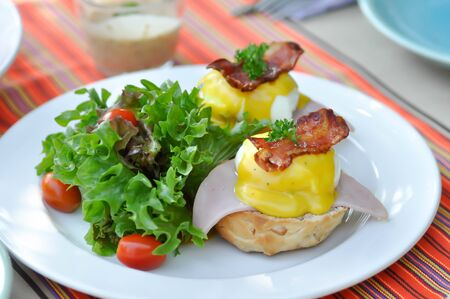 egg benedict or bun with egg , ham and bacon topping