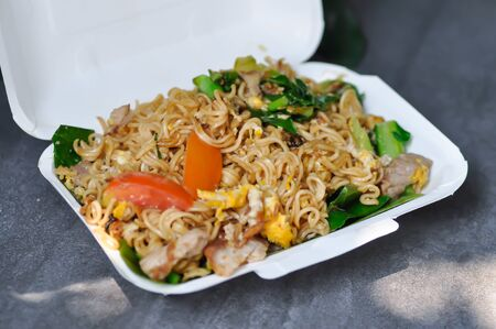 stir fried noodles with pork and vegetable in the box