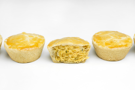 Three traditional Brazilian mini foot pies called feet side by side in white background with one open in the middle