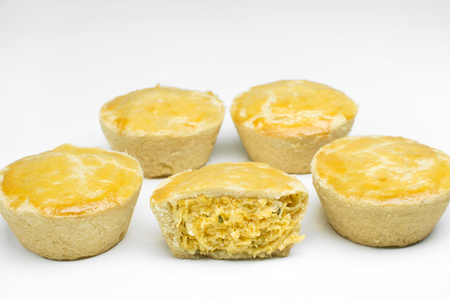 Five traditional Brazilian mini pies called pies in white background with one open in the middle