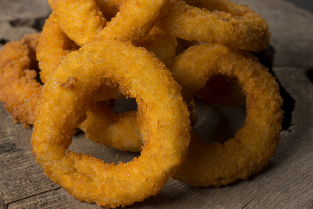 Onion rings in rustic wood background with half light