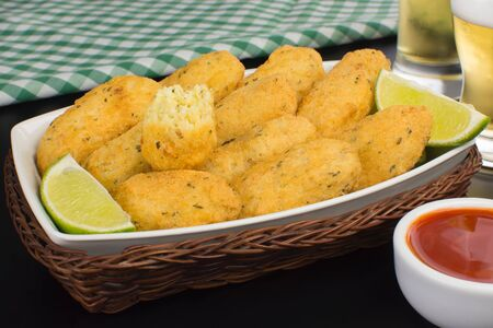 Traditional recipe codfish balls in black background with one cuted Imagens