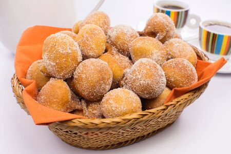 Traditional Brazilian mini fried cakes called bolinho de chuva in a basket in white breakfast table  background