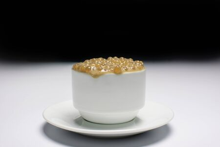 Brazilian dessert made of tapioca pearls called sagu in coffee flavor in a white cup and background