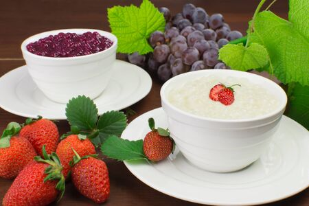 Brazilian dessert made of tapioca pearls called sagu in cream and red wine flavors with grapes and strawberries in wood background