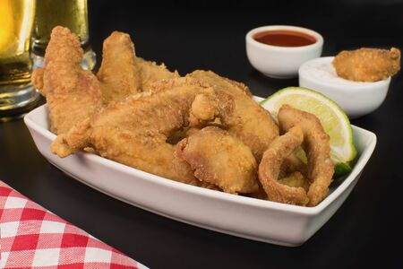 Fried Tilapia strips in platter with beer and sauces in black background
