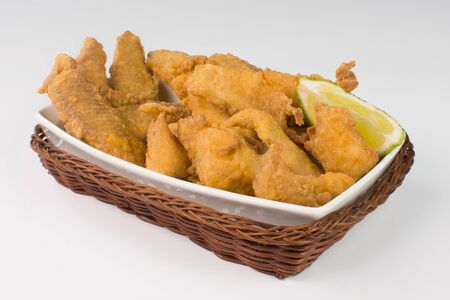 Fried Tilapia strips in platter  isolated in white background Imagens