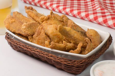 Fried Tilapia strips in platter with beer and sauces in white background with half light