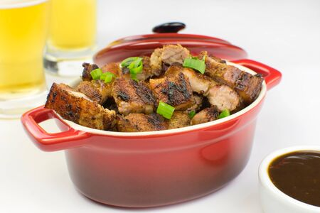 Grilled pork belly in a red bowl with barbecue salce and beer in white background
