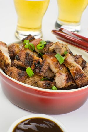 Grilled pork belly in a red bowl with barbecue salce and beer in white background close