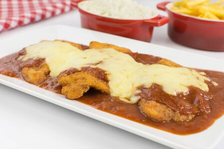 Veal parmigiana in a white platter with rice in and french fries in white background close Imagens