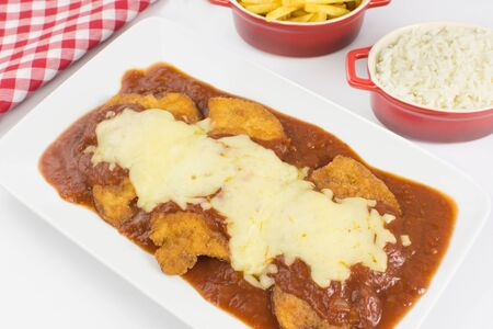 Veal parmigiana in a white platter with rice in and french fries in white background seen from above