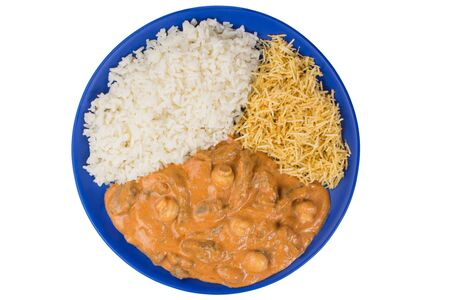 Brazilian tenderloin stroganoff with rice and potato sticks in a blue plate in white background isolated seen from above