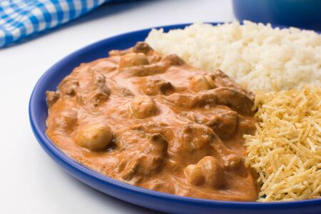 Brazilian tenderloin stroganoff with rice and potato sticks in a blue plate in white background close Imagens