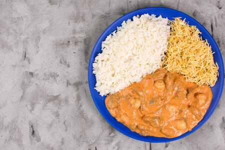 Brazilian tenderloin stroganoff with rice and potato sticks in a blue plate isolated in burnt cement background seen from above