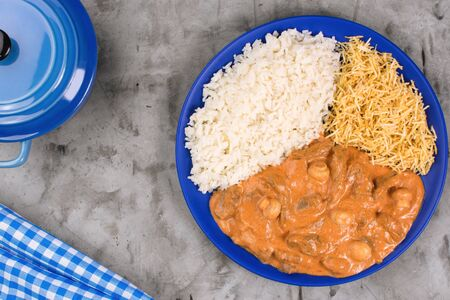 Brazilian tenderloin stroganoff with rice and potato sticks in a blue plate in burnt cement background seen from above Imagens