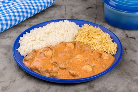 Brazilian tenderloin stroganoff with rice and potato sticks in a blue plate in burnt cement background