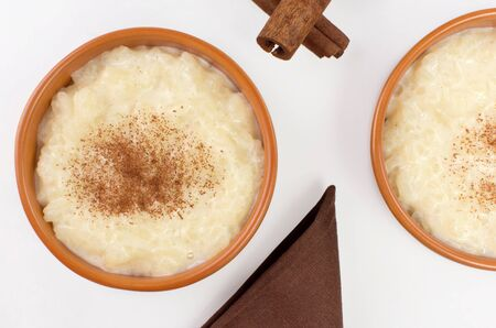 Traditional June party Brazilian dessert made of rice and condensed milk called arroz doce in white background seen from above